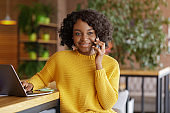 Successful black lady entrepreneur talking with business partner on phone