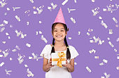 Girl Holding Birthday Gift Standing Under Falling Confetti, Purple Background