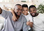 Smiling Senior Black Man Taking Selfie With Son And Grandson At Home