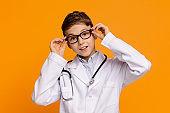 Playful teenager in medical uniform posing on orange background