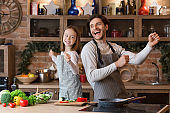 Portrait Of Cheerful Little Girl And Her Dad Dancing In Kitchen