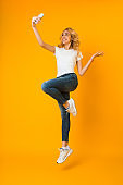 Happy woman in casual clothes jumping and making selfie
