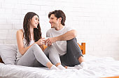 Happy newlyweds enjoying first married morning in bed