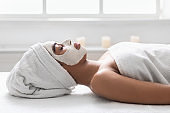 Black girl with white face mask resting on massage table