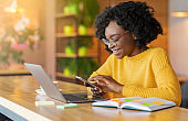 Happy black girl working online and using mobile phone