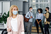 Return to work after lockdown and new normal. Woman in protective mask looks to the side in corridor of modern office with blurred colleagues