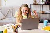 Girl sitting at desk, using laptop and waving at camera