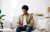Studying from home concept. Black teen guy with laptop communicating online with teacher, taking notes during lecture