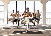 Group Of Sporty People Doing Tree Pose Exercise While Practicing Vrksasana Yoga