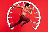 Young female sprinter running on red background. Collage with speed recorder. Panorama