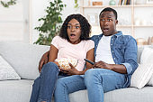 Shoxked african man and woman watching horror at home