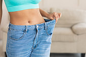 Unrecognizable Woman Wearing Big Jeans After Diet And Slimming Indoor