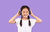 Little Japanese Girl In Earphones Enjoying Music On Purple Background