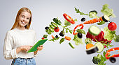 Caucasian woman with tablet using meal planning app, collage with flying vegetables, grey background. Copy space