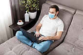 Home work place. Man freelancer in face surgical mask working from home using laptop. Cozy home office on sofa. Coronavirus covid-19 social distancing self quarantine, Stay home isolation concept