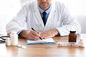 Close up of medical practitioner filling in paperwork