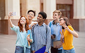 Multiracial students talking selfie using cell phone