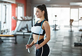 Attractive young woman with jumping rope in sports club