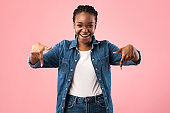 Joyful Black Girl Pointing Fingers Down Posing On Pink Background