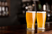 Event beer in pub. Two glasses of ale on bar in interior