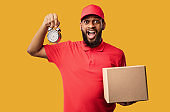 African American Courier Holding Clock Delivering Cardboard Box, Studio Shot