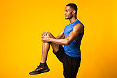 Young black sportsman walks highly holding knee