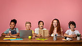 Remote schooling. Group of boys and girls with learning materials and devices sitting at desk over pink background