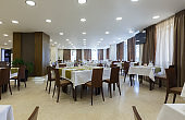 Tables in hotel restaurant with wooden chairs