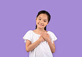 Thankful Chinese Girl Pressing Hands To Chest Over Purple Background