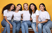 Cheerful Girls Friends Hugging Sitting On Bench On Yellow Background