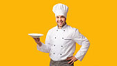Smiling Cook Guy Holding Plate Standing Over Yellow Background, Panorama