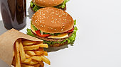 Home delivery and american fast food takeaway. Cheeseburger and hamburger, french fries in eco pack and glass of cola, isolated on white background