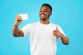 African American Man Making Selfie Gesturing Thumbs-Up Over Blue Background