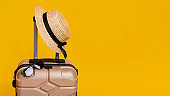 Summer Travel. Suitcase with sun glasses and hat over yellow background
