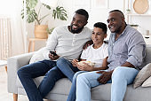 Cheerful african grandpa, father and son relaxing together in living room