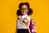 Smiling African Schoolgirl Pointing Finger At Camera Standing, Studio Shot