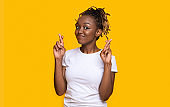 Excited black girl crossing fingers, making wish on yellow