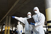 Men in special virus protective suits making research of coronavirus availability