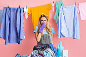 Housewife closes nose in front of heap of dirty clothes