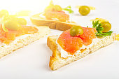 Appetizer, open sandwich with salmon and soft cheese on white background. Traditional Italian or Scandinavian cuisine. Concept of proper nutrition and healthy eating. Flat lay, copy space for text