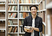 Smiling korean guy holding textbooks at library