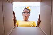 Excited african woman unpacking carton box at home