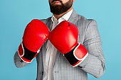 Business competition. Unrecognizable entrepreneur in boxing gloves on blue background, closeup