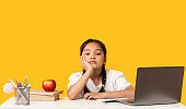 Asian School Girl Sitting At Laptop Doing Homework, Yellow Background
