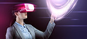 Businesswoman in virtual reality headset touching vitrual screen with data on dark background, collage