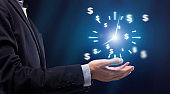 Time is money. Businessman's hand holding virtual clock with money icons