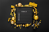 Numbered list of 2021 Goals on black Board in frame made of gold festive decor, gift boxes, confetti. New year eve 2021 goals, resolution check list with motivation or wishlist. Flat lay Copy space