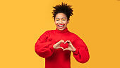 Smiling afro woman showing heart gesture at studio