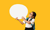 Japanese Schoolgirl Holding Blank Speech Bubble Standing Over Yellow Background