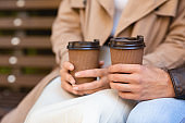 Man and woman sitting on bench, drinking coffee, cropped